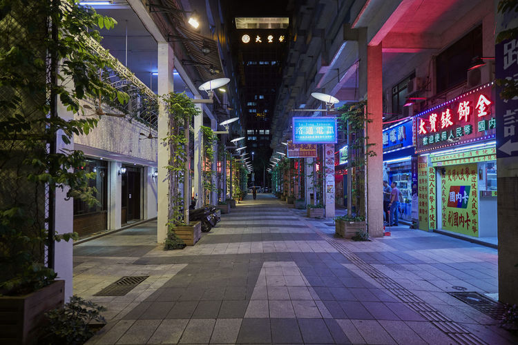 Illuminated footpath amidst buildings in city at night