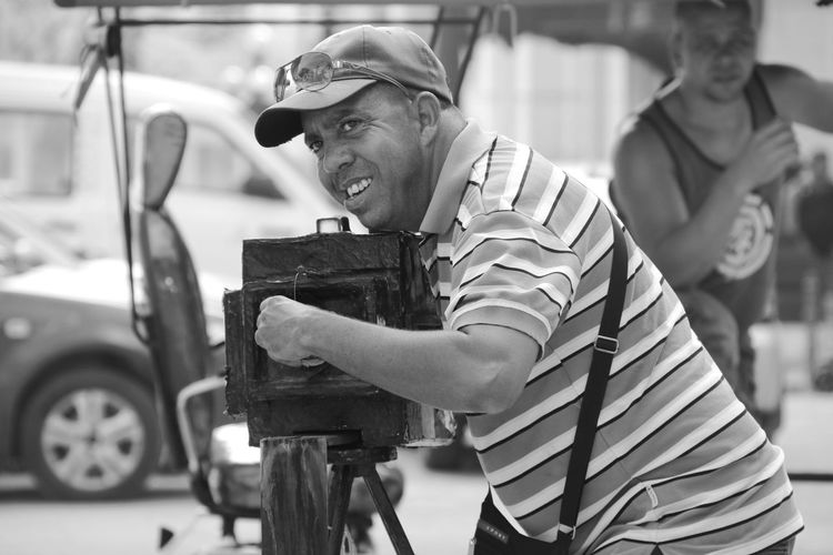 Side view of photographer adjusting his camera on tripod
