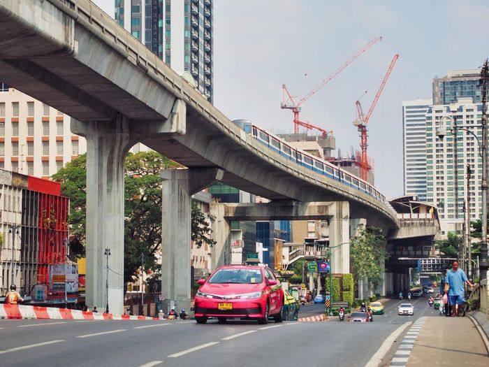 Vehicles on road by buildings against sky
