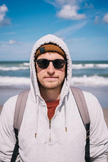 Portrait of mature man wearing sunglasses against sea