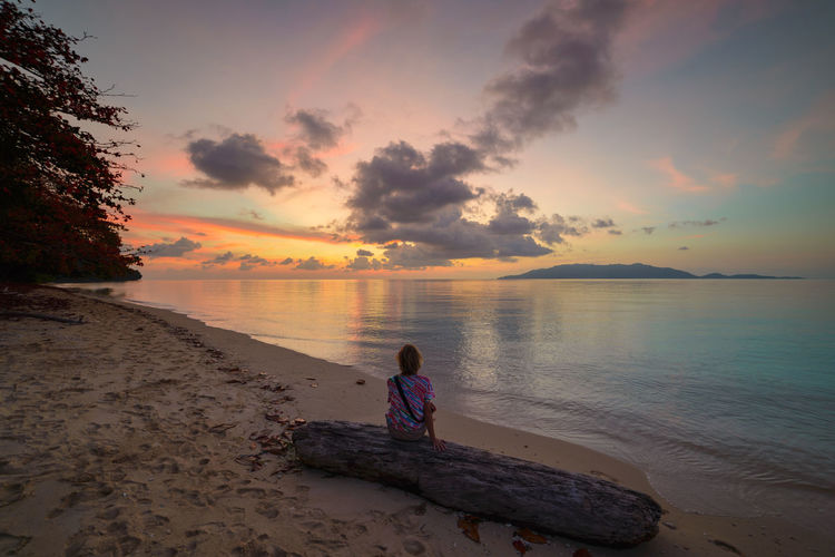 Water Sunset Sky Sea Beach Beauty In Nature Land Scenics - Nature Real People Cloud - Sky Leisure Activity One Person Lifestyles Rear View Tranquility Horizon Over Water Horizon Tranquil Scene Sitting Outdoors