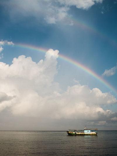 Boat sailing in sea against rainbow in sky