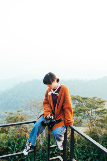 Young asian woman with casual clothes sit on fence in morning light holding camera at mountain top