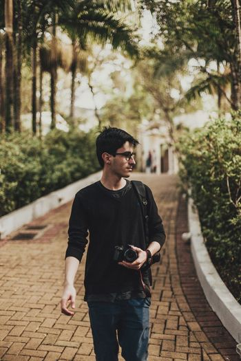Young man looking away while standing on footpath