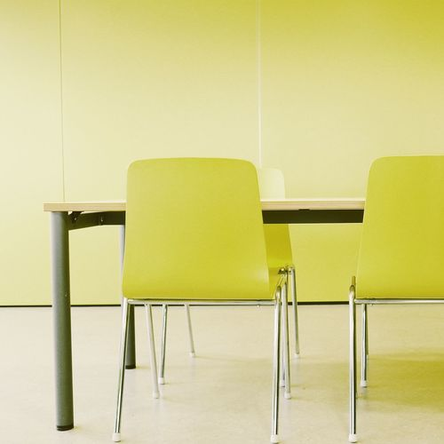 Table with yellow chairs against wall