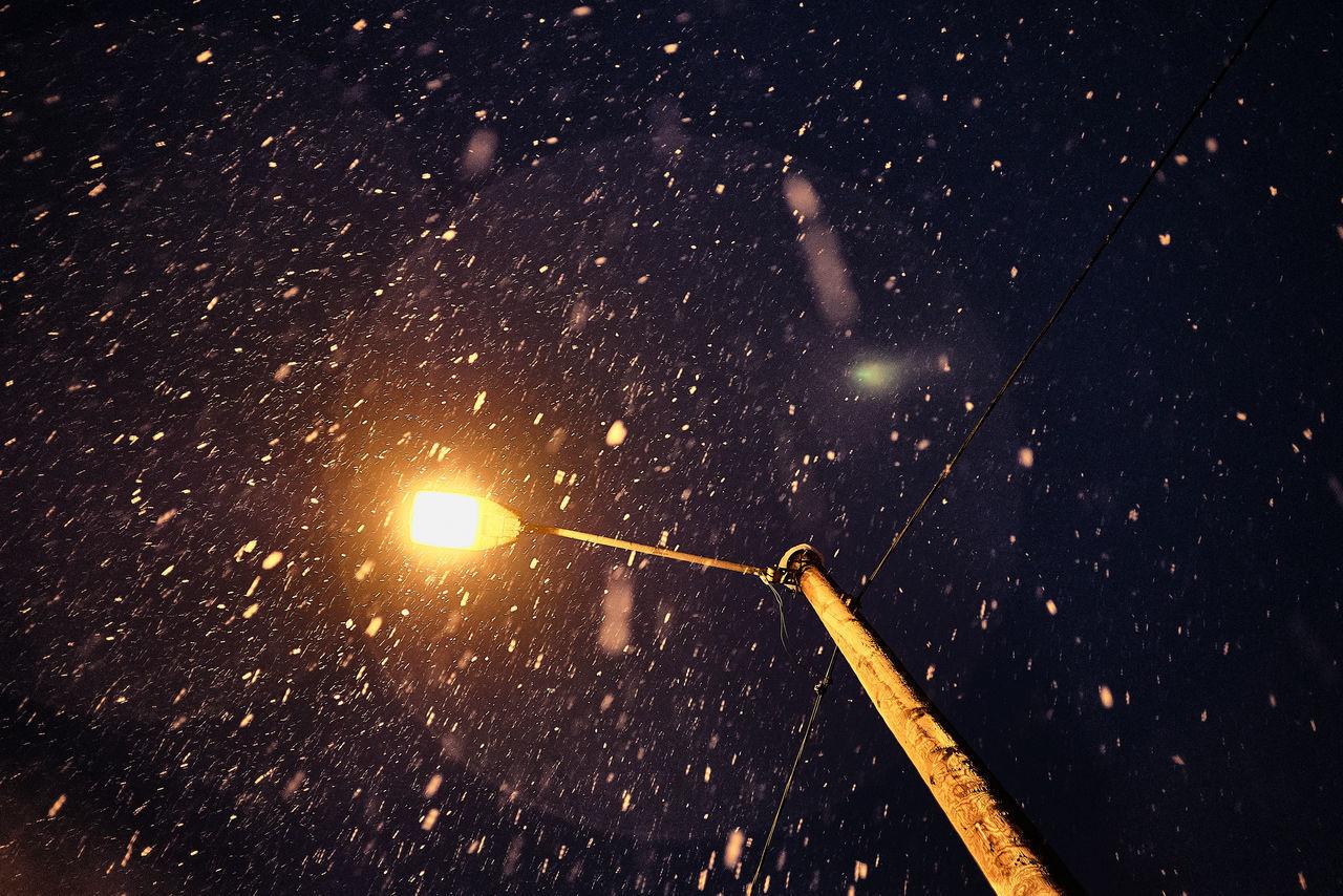 ILLUMINATED STREET LIGHT AGAINST SKY DURING WINTER