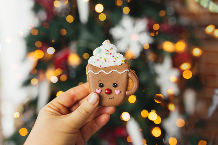 Hand holding christmas gingerbread cookie and decorations at christmas tree, gingerbread cup