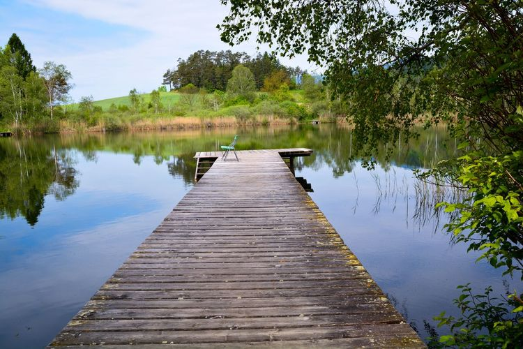 Wooden jetty on pier over lake against sky
