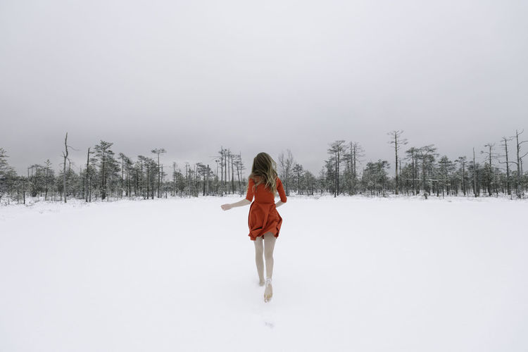 Rear view of woman on snow covered field against sky