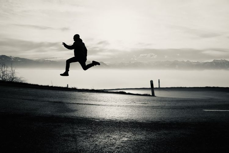 Silhouette man jumping on road against sky