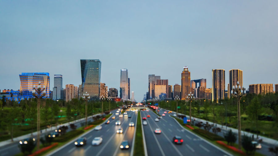 Traffic on highway by buildings in city against sky