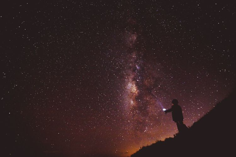 Low angle view of silhouette man standing against star field