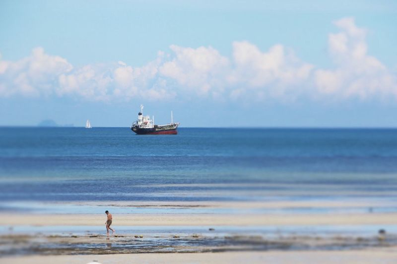 Man walking down beach with ship in the distance