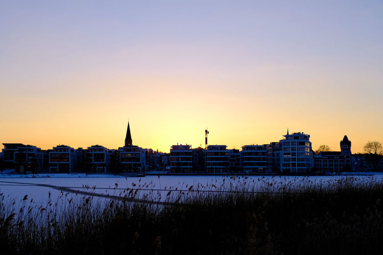 Buildings in city at sunset