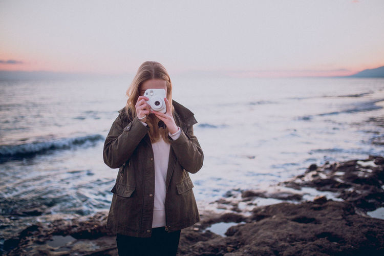 Young woman taking picture with her retro camera of breathtaking sunset at the beach EyeEm Best Shots EyeEm Nature Lover EyeEm Selects EyeEm Gallery EyeEmNewHere Freedom Fun Hanging Out Instax Life Memories Nature Retro Sunset_collection Vibes Beach Evening Lifestyles Ocean Sky Summer Sun Sunset