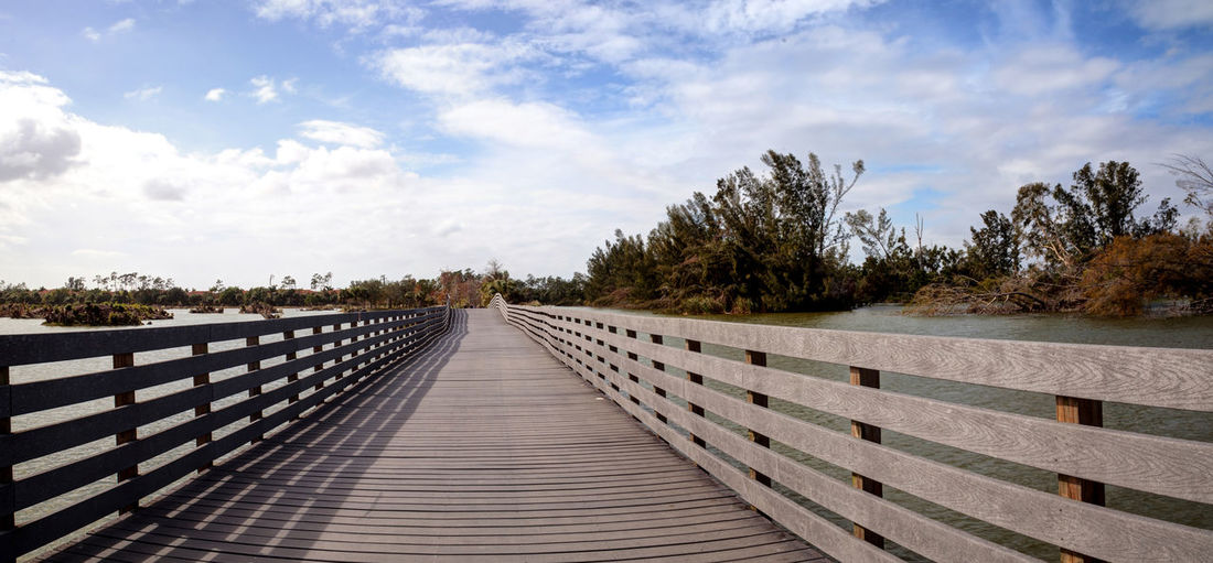 Boardwalk goes through the swamp at Lakes Park in Fort Myers, Florida and displays the damage done by hurricane Irma with uprooted trees. Damage Destruction Fort Myers Hurricane Irma Pond Swamp Trees Beauty In Nature Boardwalk Cloud - Sky Day Florida Footbridge Nature No People Outdoors Railing Scenics Sky Topple Tranquility Tree Uprooted Wood - Material Wood Paneling