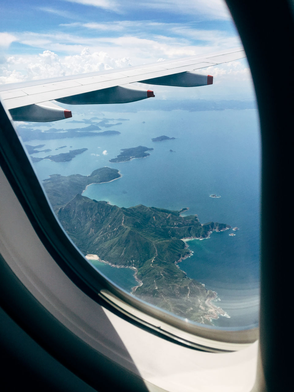 airplane, airplane wing, aerial view, journey, transportation, flying, air vehicle, travel, landscape, window, mid-air, aircraft wing, mode of transport, sea, sky, nature, cloud - sky, no people, day, scenics, mountain, beauty in nature, vehicle part, indoors, close-up