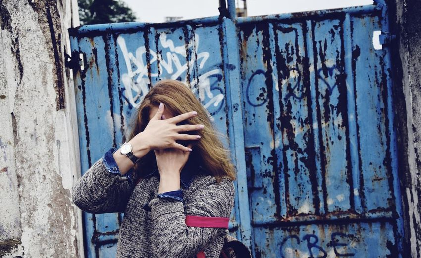 Woman covering face with hands against closed old gate