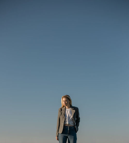 Woman standing against clear blue sky