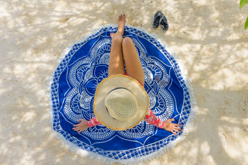 Directly Above Shot Of Woman Wearing Hat While Sitting On Beach Towel