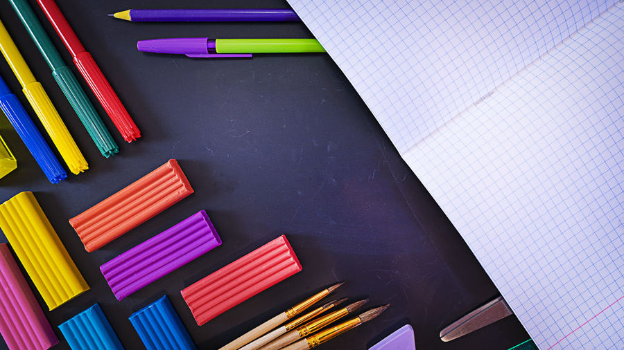 Concept back to school, school supplies on black chalkboard with an open notebook, top view