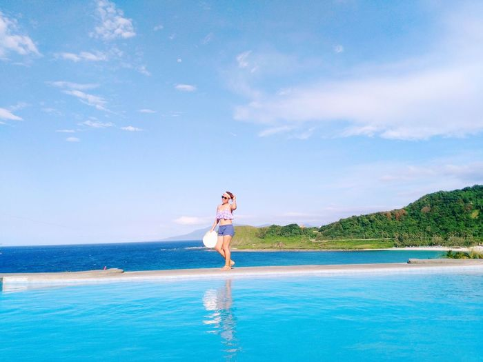Full length of woman by infinity pool at beach