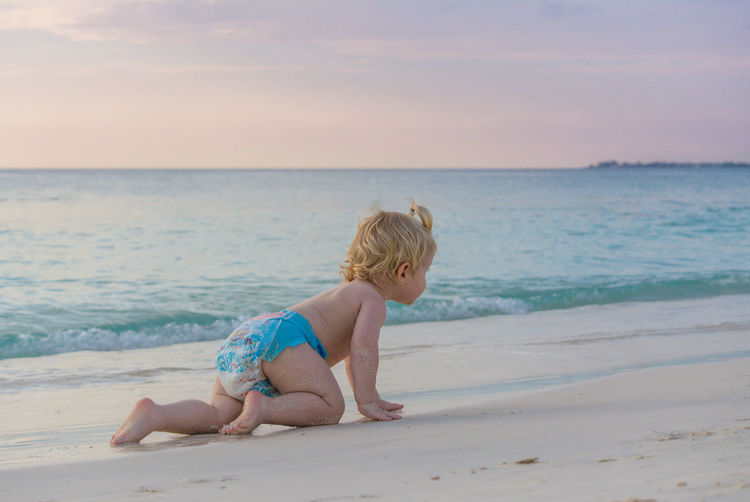 Full length of shirtless boy crawling at beach against sky