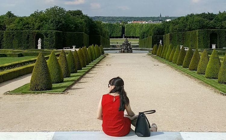 Versailles Palace Versailles Gardens One Person One Woman Only Outdoors Tree Day Shadow EyeEmNewHere Sky Textures And Surfaces Old-fashioned Travel Destinations Statues/sculptures Travel Scenics Green Color Tree Lined