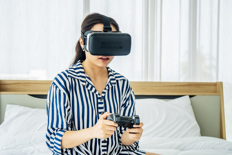 Young woman using vr goggles on bed