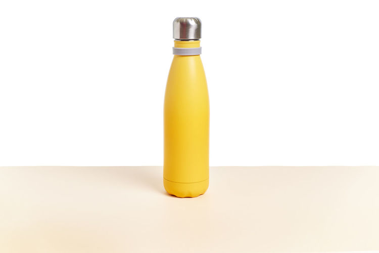 Close-up of yellow bottle against white background
