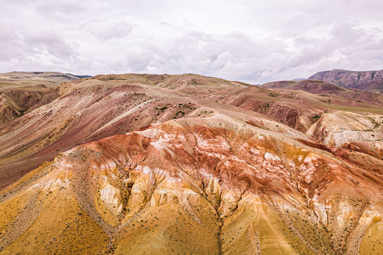 A stunning panorama of a mountain chain of peaks, a canyon with red clay, top view.