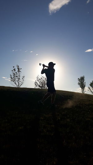 Silhouette Man Playing Golf On Field During Sunset