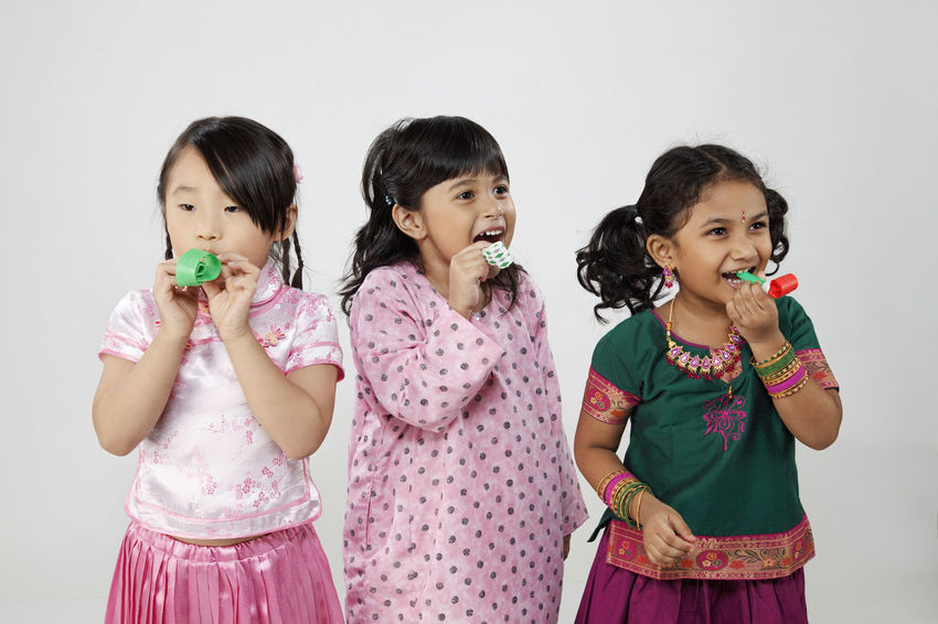 malaysia multi racial girl blowing noise maker Celebration Happiness Indian Traditional Clothing Child Childhood Chinese Females Front View Harmony Holding Indoors  Innocence Malay Ethnicity Malaysia Malaysian Multi Racial Noise Makers Party Portrait Smiling Standing Togetherness White Background Women