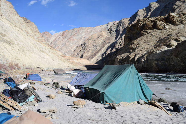 Tents at campsite on zanskar riverbank amidst rocky mountains