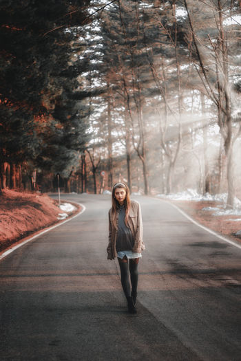 Portrait of young woman standing on road amidst trees