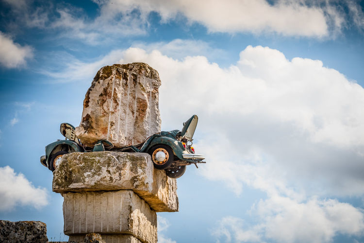 Low angle view of car crushed under rocks against cloudy sky