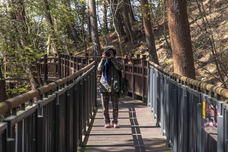 Woan taking a photo on footbridge
