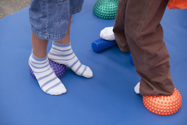 Low Section Of Children Wearing Socks Standing On Spiked Balls While Exercising In Gym