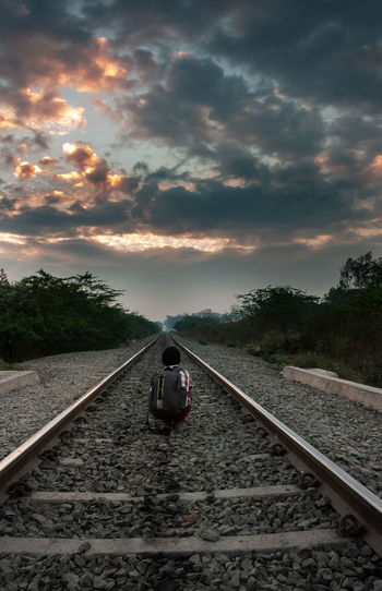 Rear view of person on railroad tracks against sky during sunset
