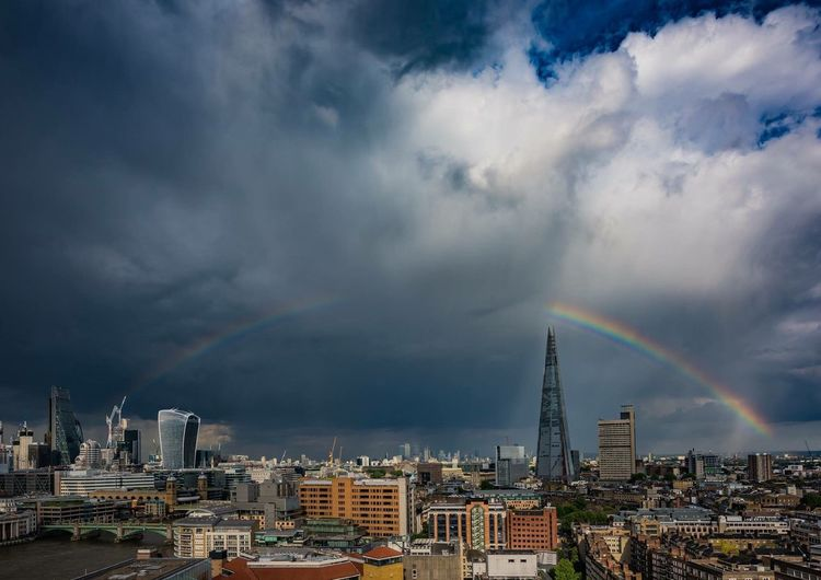 View of rainbow over city against cloudy sky