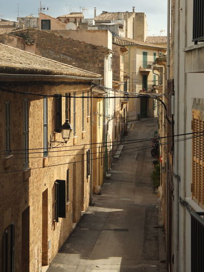 A beautiful mediterranean view in some streets on the island of Mallorca Street Arch Alley Narrow Railing Diminishing Perspective No People Old Outdoors Day City Residential District Building Direction The Way Forward Building Exterior Built Structure Architecture Mallorca Lifestyles