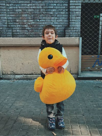 Full length of playful boy with stuffed duck
