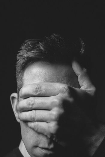 Close-Up Of Man Covering Eyes Against Black Background