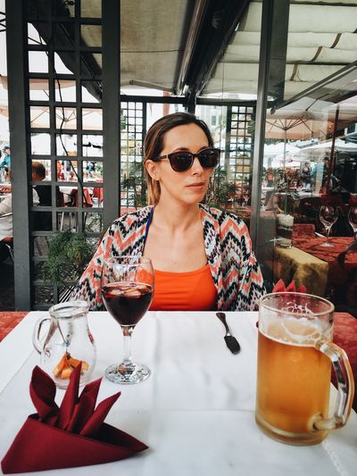 Beautiful Woman Wearing Sunglasses While Sitting At Restaurant