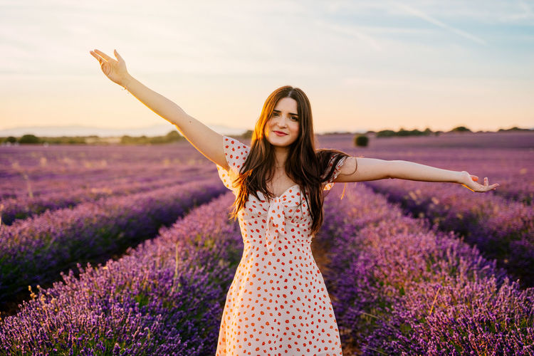 Portrait of woman with arms outstretched standing on lavender field