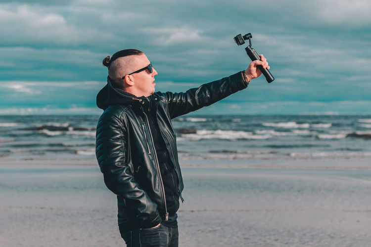 Young man wearing leather jacket filming with video camera against sea