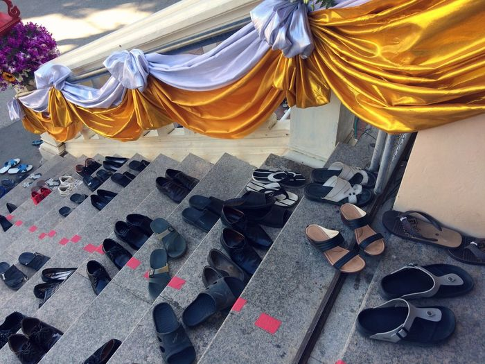 High angle view of shoes and sandals on steps at temple