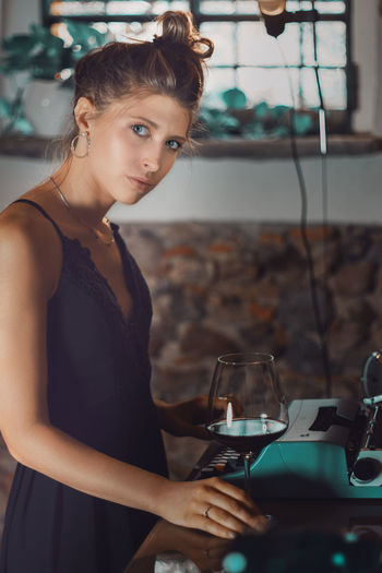 Portrait of young woman standing by typewriter and wineglass on table