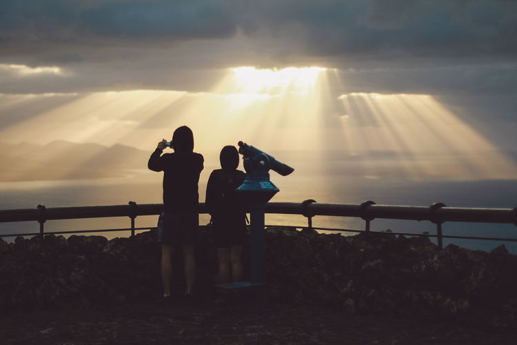 Silhouette couple standing by coin-operated binoculars with sea in background against cloudy sky