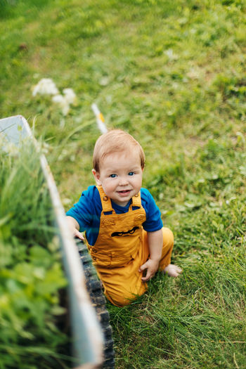 Kid sitting on the grass next to a garden cart and smiling